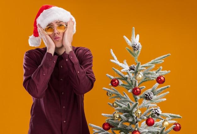 Triste giovane uomo biondo che indossa santa cappello e occhiali in piedi vicino all'albero di natale decorato su sfondo arancione