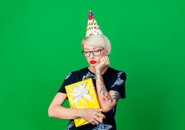 Sad young blonde party girl wearing glasses and birthday cap holding gift box looking down isolated on green background with copy space