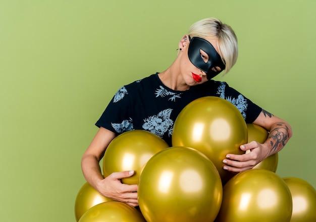 Triste giovane ragazza bionda party indossando la maschera di travestimento in piedi dietro palloncini afferrandoli guardando verso il basso isolato su sfondo verde oliva con lo spazio della copia