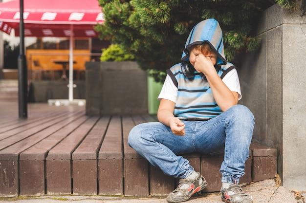 계단에 앉아 줄무늬 스웨터에 슬픈 어린 소년