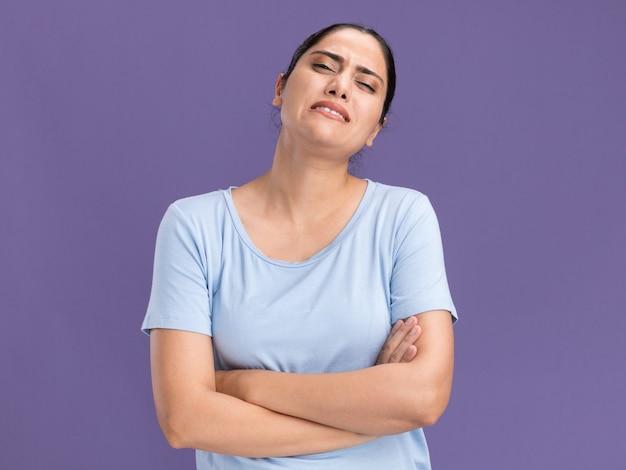 Triste giovane ragazza caucasica bruna in piedi con le braccia incrociate