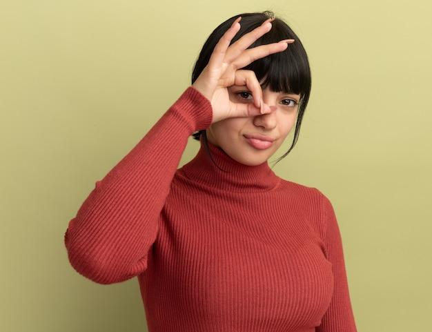 コピースペースとオリーブグリーンの壁に分離された指を通して悲しい若いブルネット白人の女の子