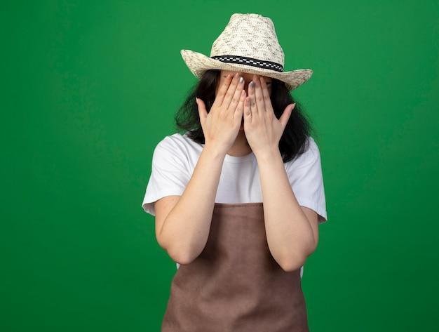 光学メガネと制服を着たガーデニング帽子の悲しい若いブルネットの女性の庭師は、緑の壁に隔離された顔に手を置きます