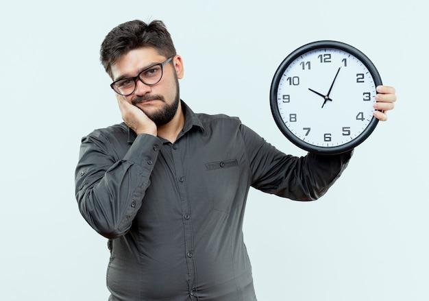 Triste giovane imprenditore con gli occhiali tenendo l'orologio da parete e mettendo la mano sulla guancia isolato su bianco