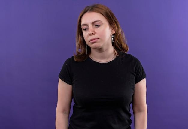 Triste giovane donna casual in piedi e guardando in basso sullo spazio viola isolato con spazio di copia