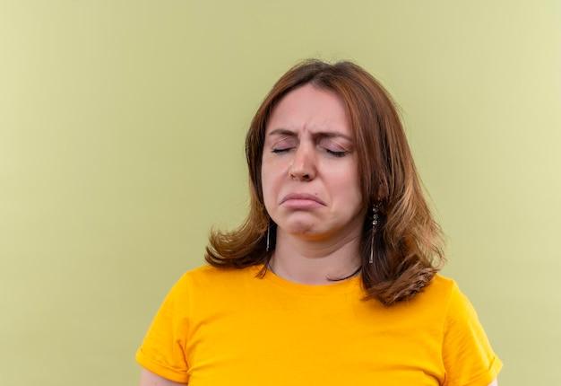 Triste giovane donna casual con gli occhi chiusi su uno spazio verde isolato con copia spazio