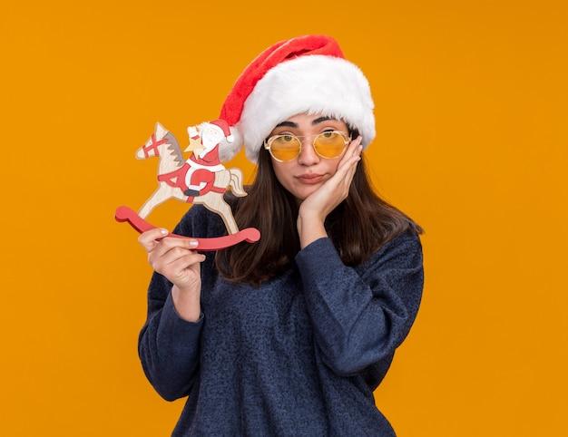 Triste giovane ragazza caucasica in occhiali da sole con cappello santa mette la mano sul viso e tiene santa sulla decorazione del cavallo a dondolo
