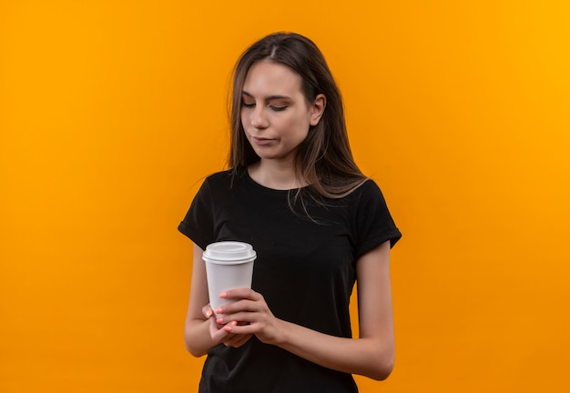 격리 된 오렌지 배경에 커피 한잔보고 검은 티셔츠를 입고 슬픈 젊은 백인 여자