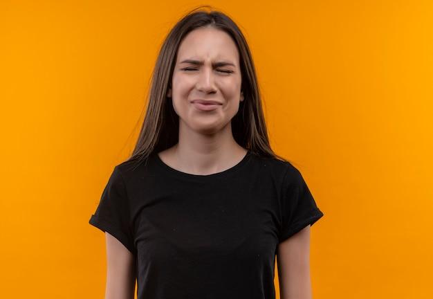 Sad young caucasian girl wearing black t-shirt with closed eyes on isolated orange background