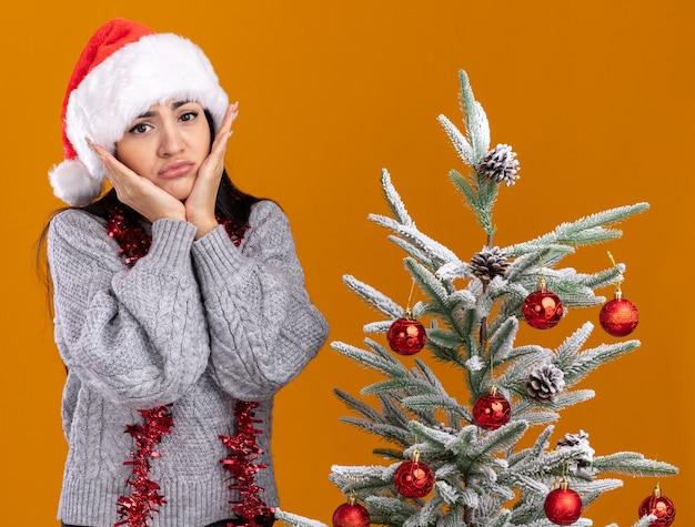Triste giovane ragazza caucasica che indossa cappello di natale e ghirlanda di orpelli intorno al collo in piedi vicino all'albero di natale decorato tenendo le mani sul viso isolato sul muro arancione