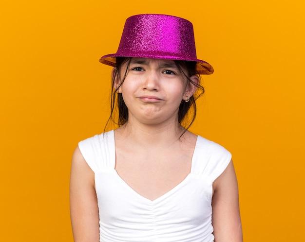 Грустная молодая кавказская девушка в фиолетовой партийной шляпе изолирована на оранжевой стене с копией пространства