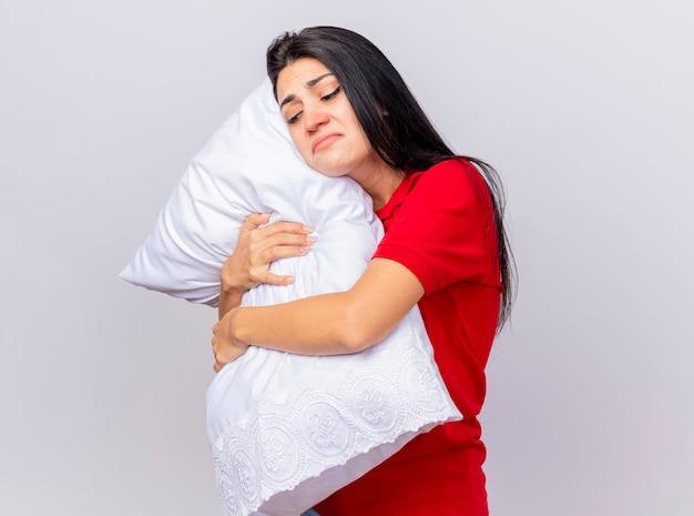 Triste giovane ragazza malata caucasica in piedi in vista di profilo abbracciando cuscino mettendo la testa su di esso guardando verso il basso isolato su sfondo bianco con spazio di copia