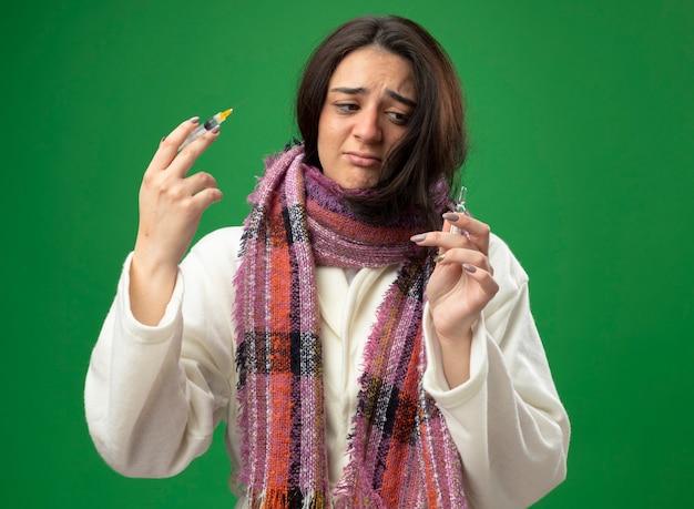 Triste giovane ragazza malata caucasica indossando accappatoio e sciarpa che tiene ampolla e siringa guardando fiala isolata sulla parete verde