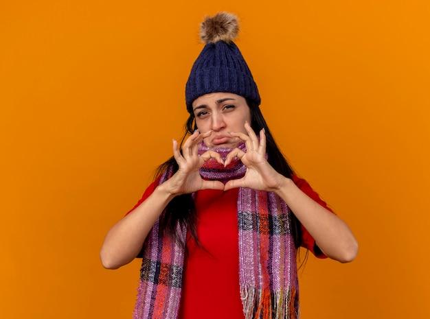 コピースペースでオレンジ色の背景に分離されたカメラを見てハートサインをしている冬の帽子とスカーフを身に着けている悲しい若い白人の病気の女の子