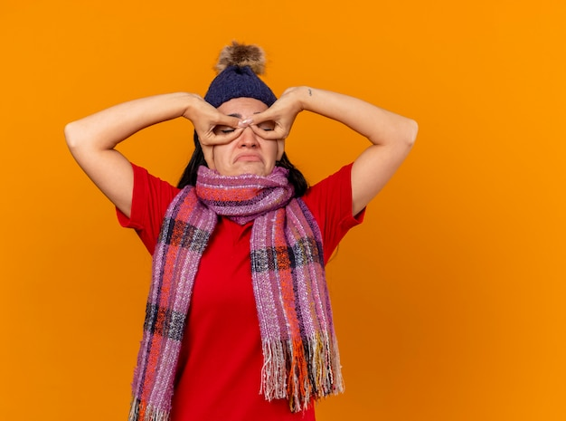Грустная молодая кавказская больная девушка в зимней шапке и шарфе делает маску руками с закрытыми глазами, изолированными на оранжевом фоне с копией пространства