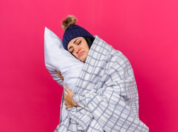 Sad young caucasian ill girl wearing winter hat and scarf wrapped in plaid hugging pillow putting head on it with closed eyes isolated on crimson background with copy space