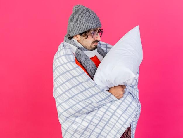 コピースペースのある深紅色の壁に隔離された枕を保持し、見ている縦断ビューで立っている格子縞に包まれた眼鏡の冬の帽子とスカーフを身に着けている悲しい若い白人の病気の男