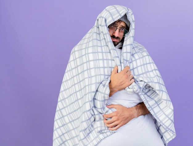 Triste giovane caucasico malato uomo con gli occhiali inverno cappello e sciarpa avvolto in plaid abbracciando il cuscino guardando la telecamera isolata su sfondo viola con spazio di copia