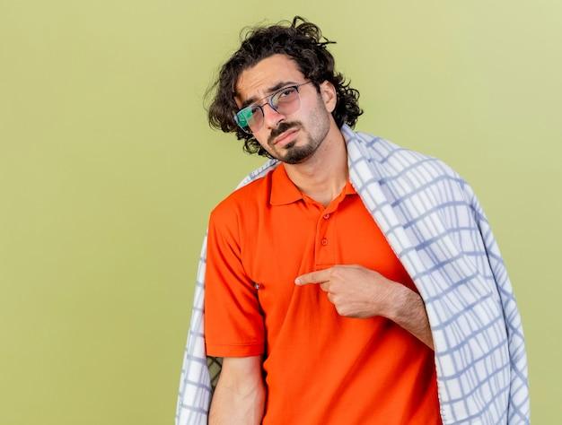 복사 공간 올리브 녹색 배경에 고립 된 측면을 가리키는 카메라를보고 격자 무늬에 싸여 안경을 쓰고 슬픈 젊은 백인 아픈 남자