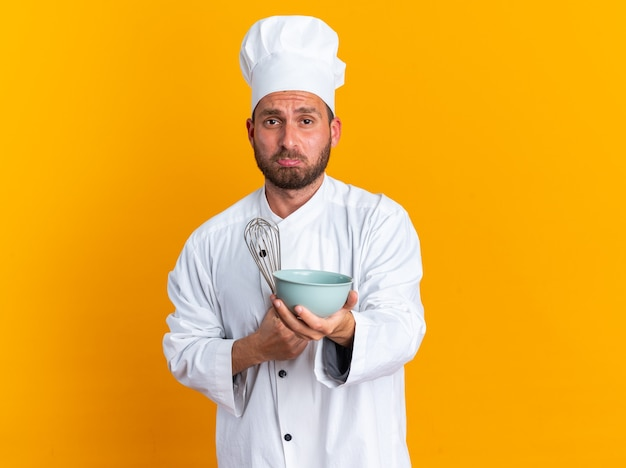 Triste giovane maschio caucasico cuoco in uniforme da chef e cappuccio che tiene la frusta che allunga la ciotola con le labbra serrate