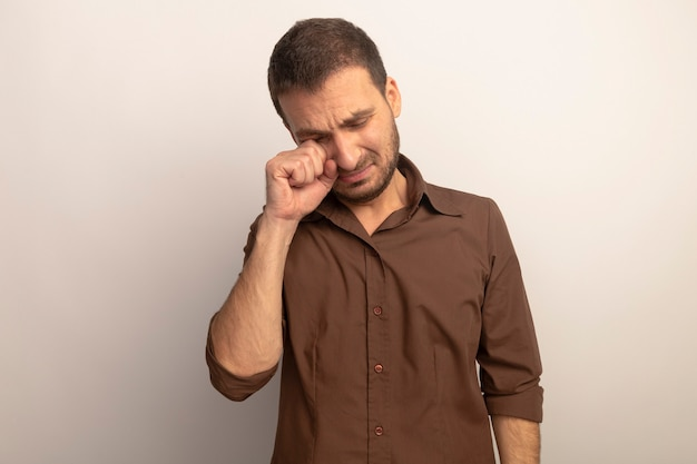 Грустный молодой кавказский мужчина вытирает глаза закрытыми глазами, изолированными на белом фоне с копией пространства