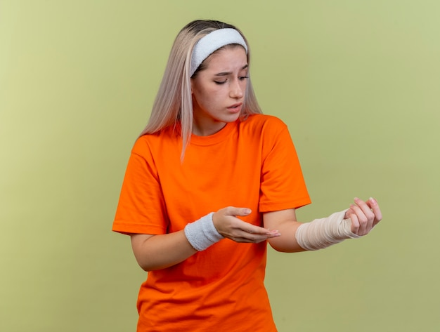 Triste giovane ragazza sportiva caucasica con bretelle che indossa fascia e braccialetti punta e guarda a portata di mano