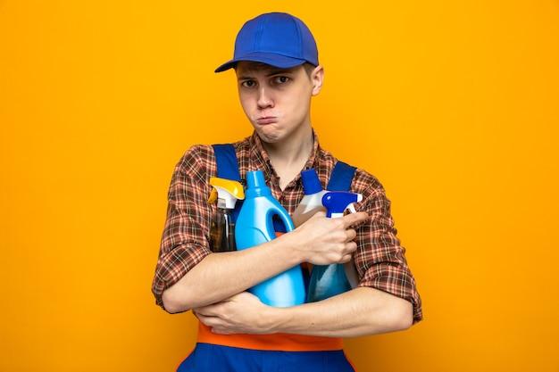 Triste giovane addetto alle pulizie che indossa l'uniforme e il berretto con gli strumenti per la pulizia