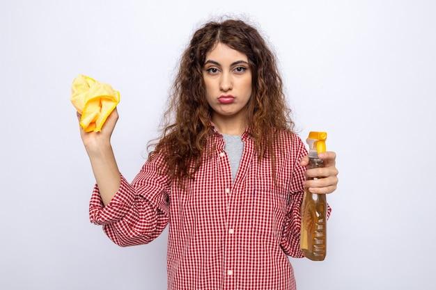 白い壁に分離されたぼろきれと洗浄剤を保持している悲しい若いクリーニング女性