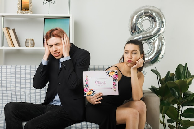 Sad young couple on happy women day holding greeting card guy putting hands on ears sitting on sofa in living room