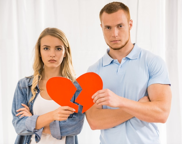 Sad young couple holding broken heart.