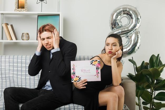 リビングルームのソファに座って耳に手を置くグリーティングカードの男を保持している幸せな女性の日に悲しい若いカップル