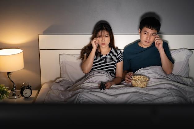 Грустная молодая пара смотрит телевизор и плачет на кровати ночью (романтический фильм)