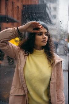 Грустная молодая кудрявая женщина остается одна за стеклом с каплями в дождливый день