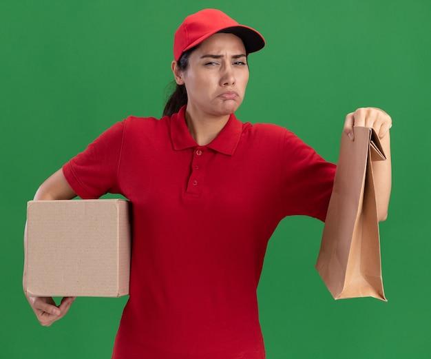 Грустная молодая доставщица в униформе и кепке держит коробку с бумажным пакетом продуктов, изолированным на зеленой стене