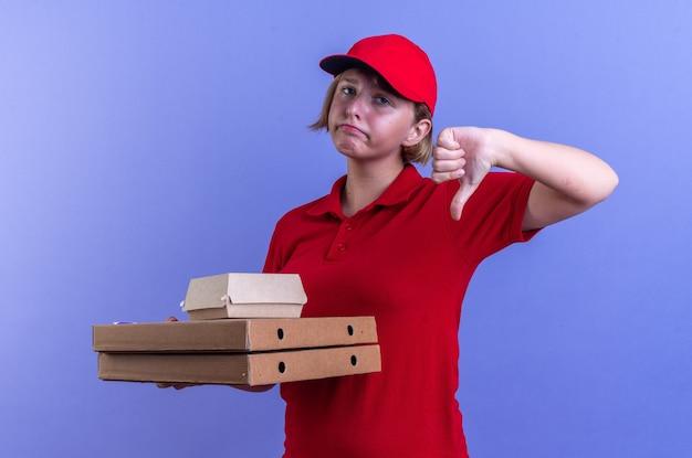 Triste giovane ragazza delle consegne che indossa l'uniforme e il cappuccio che tiene la scatola di carta per alimenti su scatole per pizza che mostra il pollice verso il basso isolato sulla parete blu