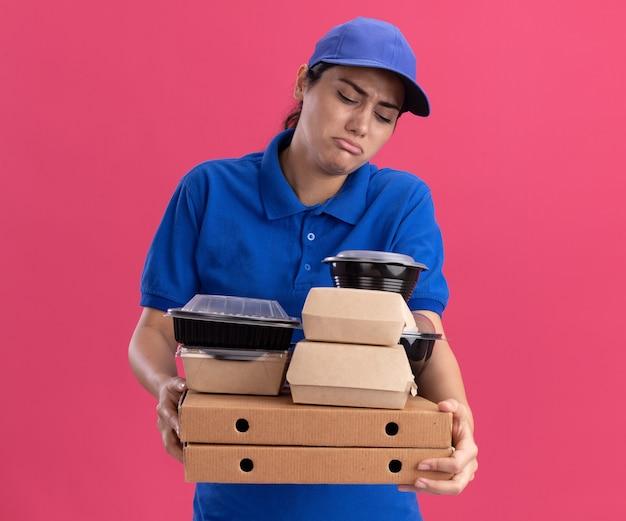 Triste giovane ragazza delle consegne che indossa l'uniforme con il cappuccio che tiene i contenitori per alimenti su scatole per pizza isolate su parete rosa