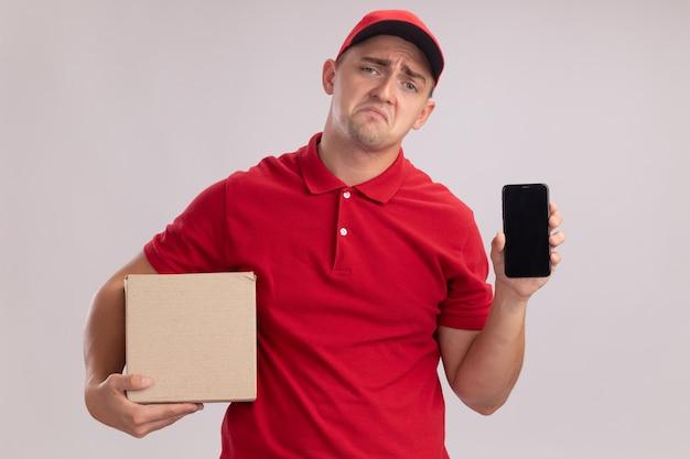 Giovane fattorino triste che indossa l'uniforme con la scatola della tenuta del cappuccio e il telefono isolati sulla parete bianca