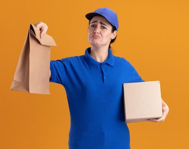 Triste giovane donna delle consegne in uniforme e cappuccio che tiene scatola di cartone e pacchetto di carta guardando la parte anteriore isolata sulla parete arancione orange
