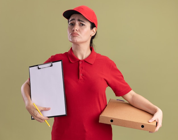 Triste giovane donna delle consegne in uniforme e berretto che tiene un pacchetto di pizza che mostra appunti con la matita in mano guardando la parte anteriore isolata sul muro verde oliva
