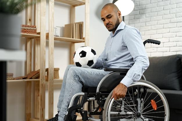 Грустный молодой человек-инвалид в инвалидной коляске с футбольным мячом