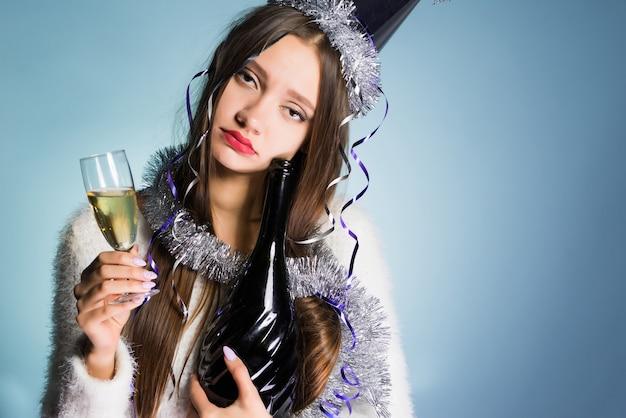 Грустная молодая пьяная девушка в кепке празднует новый год, держит в руках шампанское