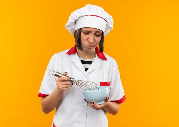 Triste giovane cuoco femminile in uniforme del cuoco unico che tiene e guardando frusta e ciotola isolato sulla parete arancione