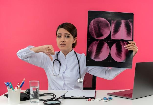 Triste giovane medico femminile che indossa abito medico con lo stetoscopio seduto alla scrivania lavora sul computer con strumenti medici tenendo i raggi x il pollice verso il basso con lo spazio della copia