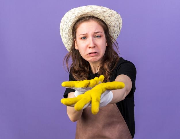 カメラで手を差し伸べる手袋でガーデニング帽子をかぶって悲しい若い女性の庭師