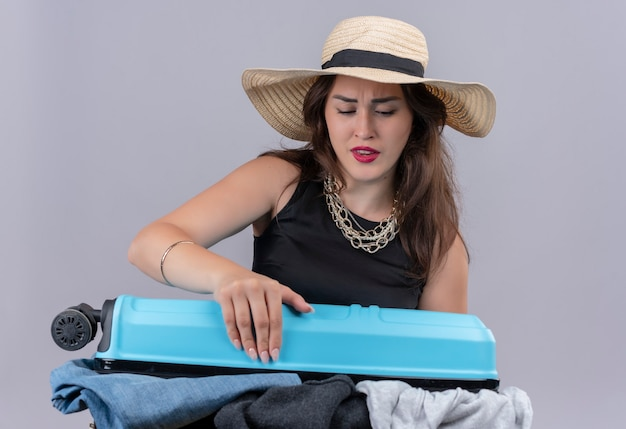 Sad young female traveler wearing black undershirt in hat holding open suitcase on white wall