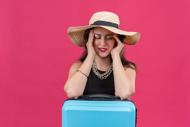 Sad young female traveler wearing black undershirt in hat put her hands on cheeks on red wall