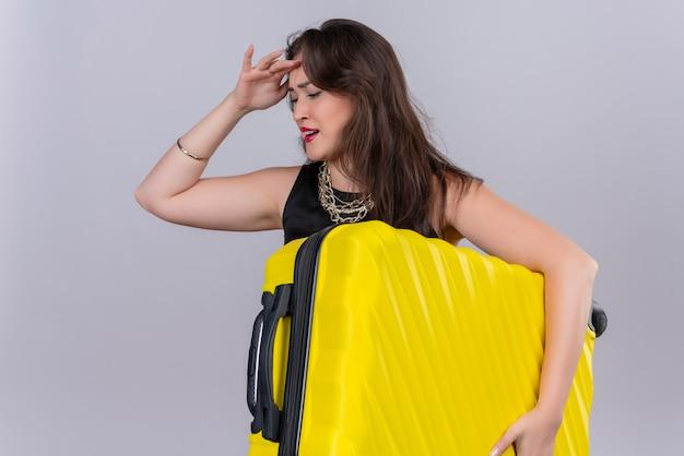 Грустная молодая женщина-путешественница в черной майке держит чемодан и положила руку на лоб на белой стене