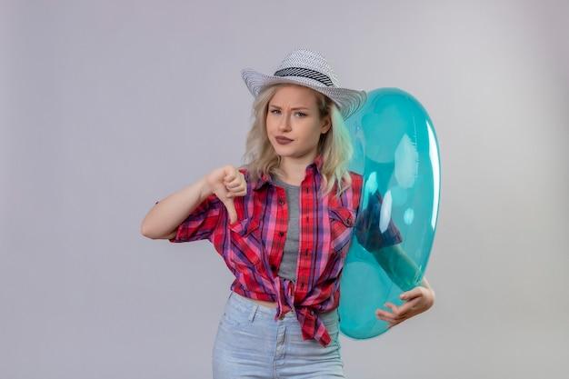 孤立した白い壁に親指を下に膨らませてリングを保持している帽子の赤いシャツを着ている悲しい若い女性旅行者