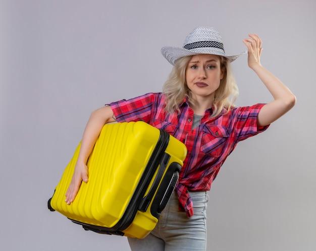孤立した白い壁にスーツケースを保持している帽子に赤いシャツを着て悲しい若い女性旅行者