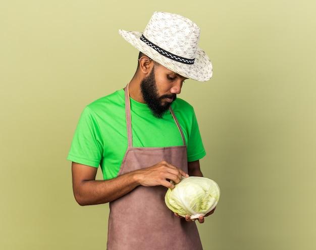 Грустный молодой афро-американский парень садовник в садовой шляпе держит и смотрит на капусту